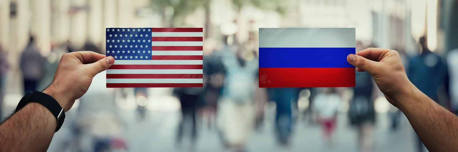 Usa vs russia. Two hands holding different flags, Russia vs United States on politics arena over crowded street background. Future strategy, relations between stock photography