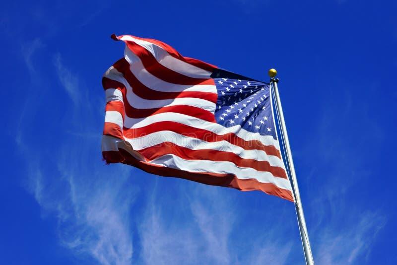 USA zaznaczają, dynamically trzepoczący w wiatrze przeciw błękitnemu chmurnego nieba tłu obraz stock