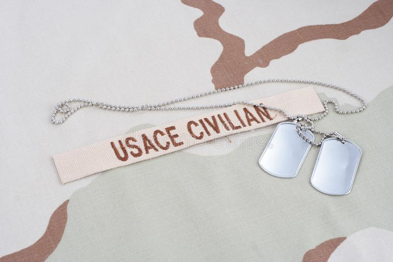 USACE CIVILAN branch tape with dog tags on desert camouflage uniform. Background stock photography