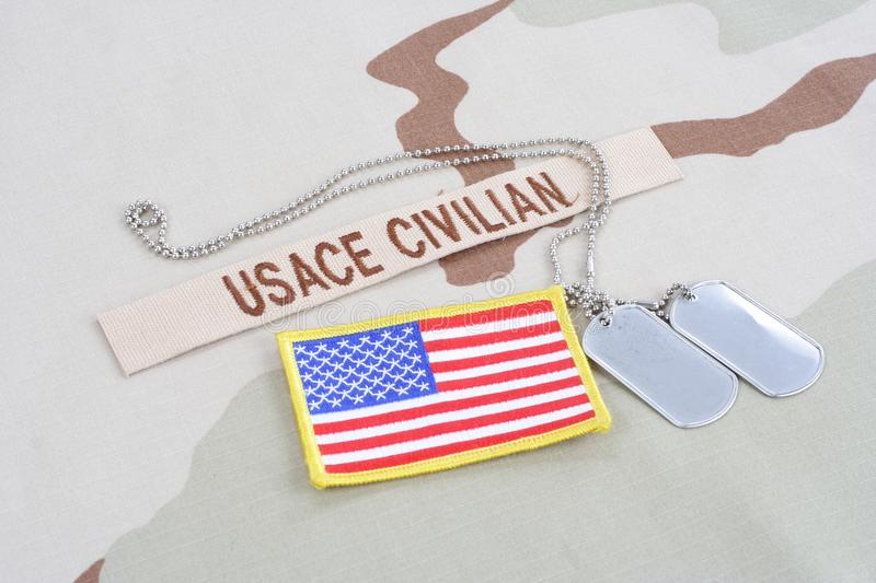 USACE CIVILAN branch tape with dog tags and flag patch on desert camouflage uniform. Background royalty free stock photo