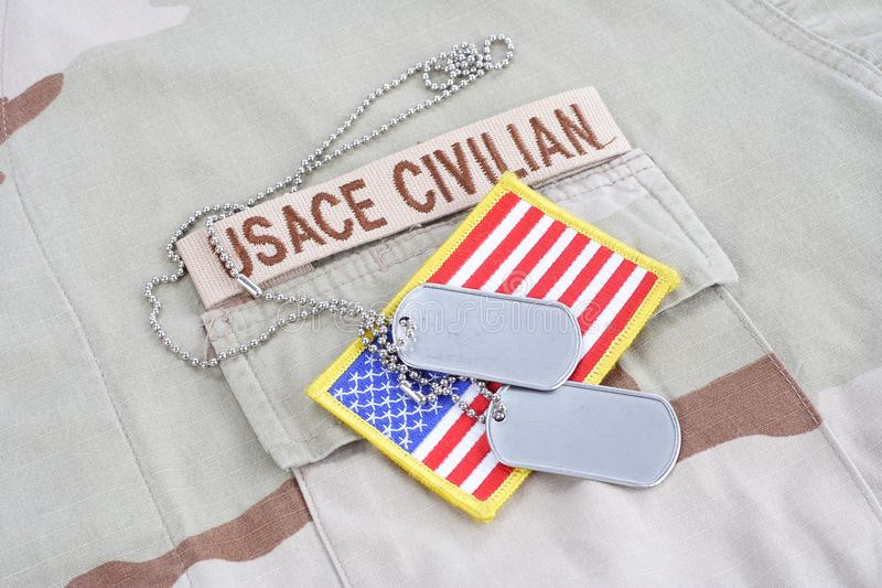 USACE CIVILAN branch tape with dog tags and flag patch on desert camouflage uniform. Background royalty free stock photos