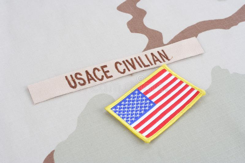 USACE CIVILAN branch tape with flag patch on desert camouflage uniform. Background stock photos