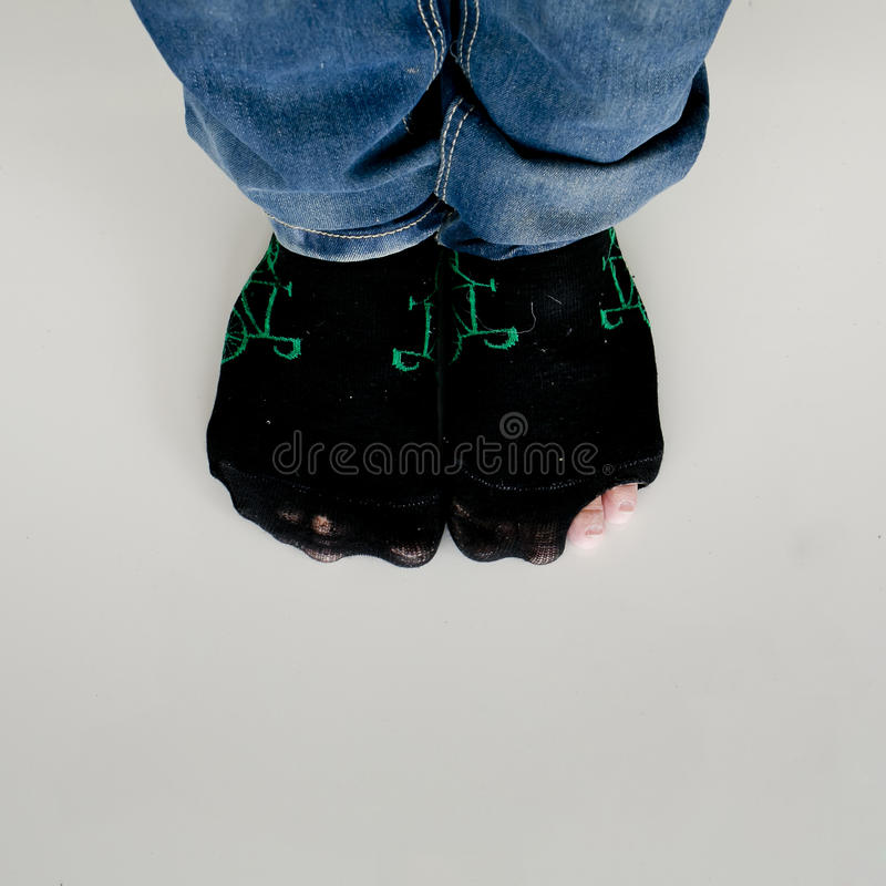 Usados calcetines con un agujero y un dedo del pie que se pegan fuera de ellos en blanco fotografía de archivo libre de regalías