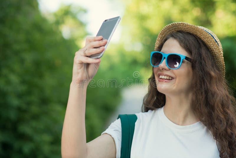 Usando a câmera do smartphone para tomar o selfie ou disparando na rua fotografia de stock