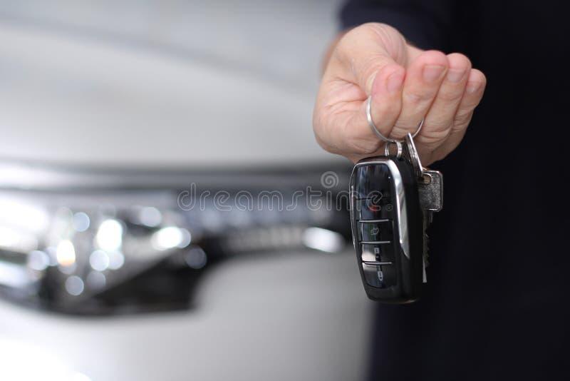 Usando a chave remota do carro do assistente para fora a parte dianteira do carro fotografia de stock