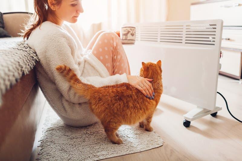 Usando el calentador en casa en invierno El calentarse de la mujer y té de consumición con el gato Época en que la calefacción se foto de archivo libre de regalías