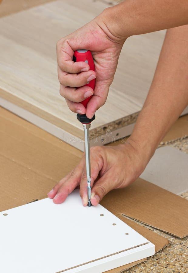 Usando el destornillador Assembling Wooden Furniture foto de archivo libre de regalías