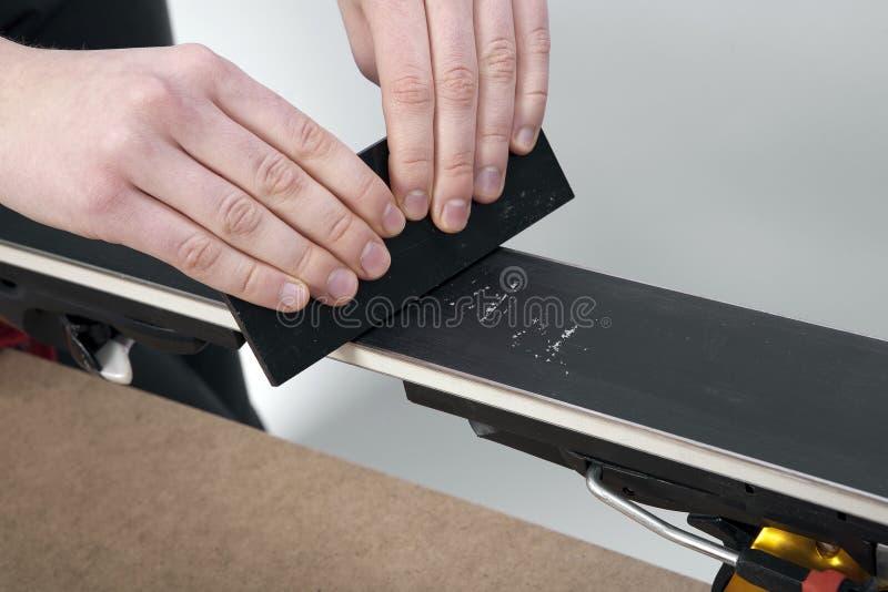 Usando el raspador plástico de la cera en base del esquí imagen de archivo libre de regalías