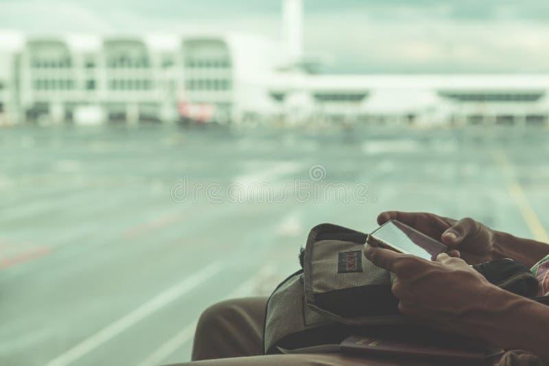 Usando el teléfono en el aeropuerto Manos de la mujer que llevan a cabo el teléfono elegante, los aviones defocused y el terminal foto de archivo libre de regalías