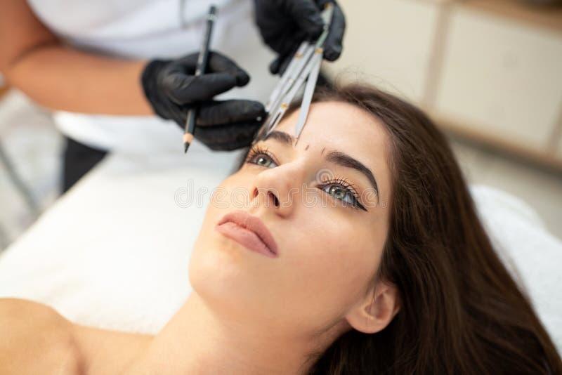 Usando ferramentas dos cosméticos para tomar a medida correta das sobrancelhas futuras imagens de stock royalty free