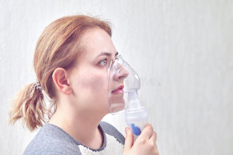 Usando la cámara del nebulizador para parar ataque de asma foto de archivo