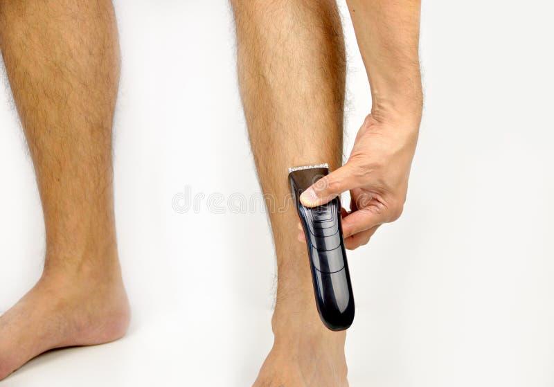 Usando la maquinilla de afeitar eléctrica en las piernas imagen de archivo