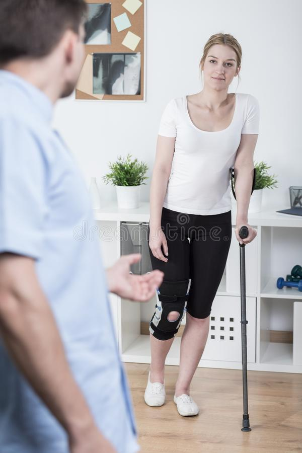 Usando la muleta después de la lesión de rodilla fotos de archivo libres de regalías
