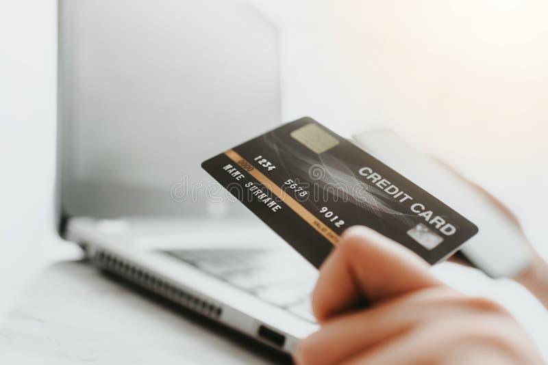 Usando la tarjeta de crédito para las compras o el pago en línea fotos de archivo