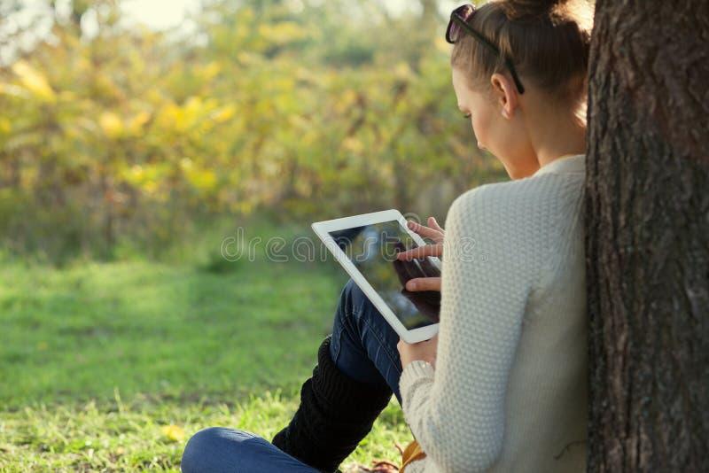 Usando mujer joven del ipad en el parque