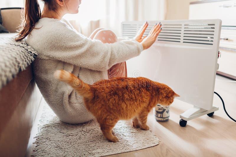 Usando o calefator em casa no inverno Mulher que aquece suas mãos com gato Estação de aquecimento imagens de stock royalty free
