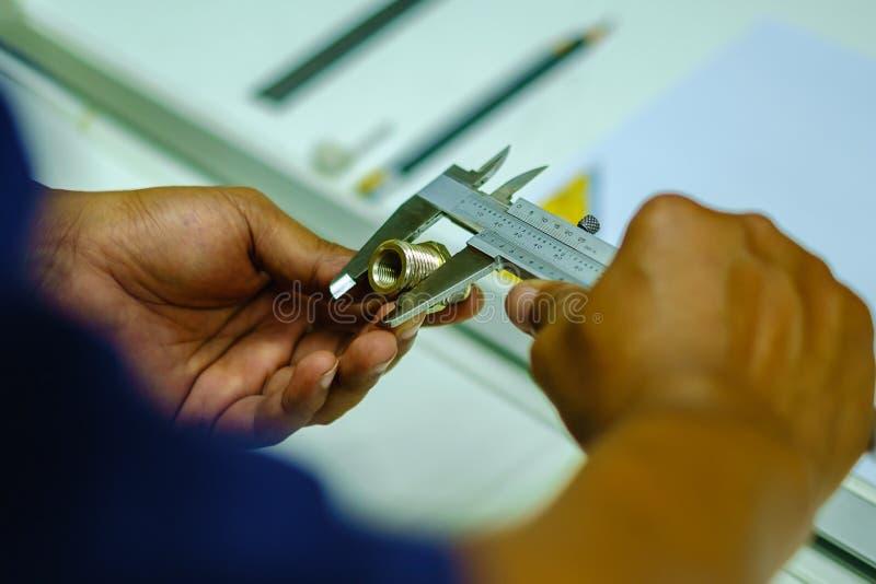 Usando o compasso de calibre vernier para medir o objeto fotografia de stock