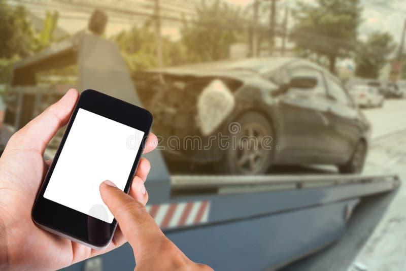Usando o smartphone disponível com o carro obscuro do fundo no acidente fotos de stock