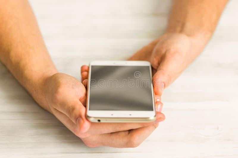 Usando Smartphone Cartão em linha do plástico dos pagamentos as mãos espertas do telefone da tela branca do smartphone fecham-se  imagens de stock royalty free