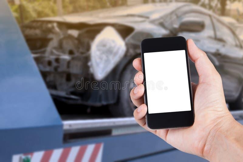 Usando smartphone a mano con el coche borroso del fondo en accidente foto de archivo libre de regalías
