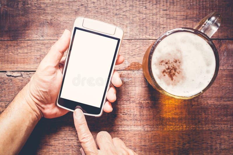 Usando smartphone por otra parte de la cerveza en el pub imagen de archivo libre de regalías