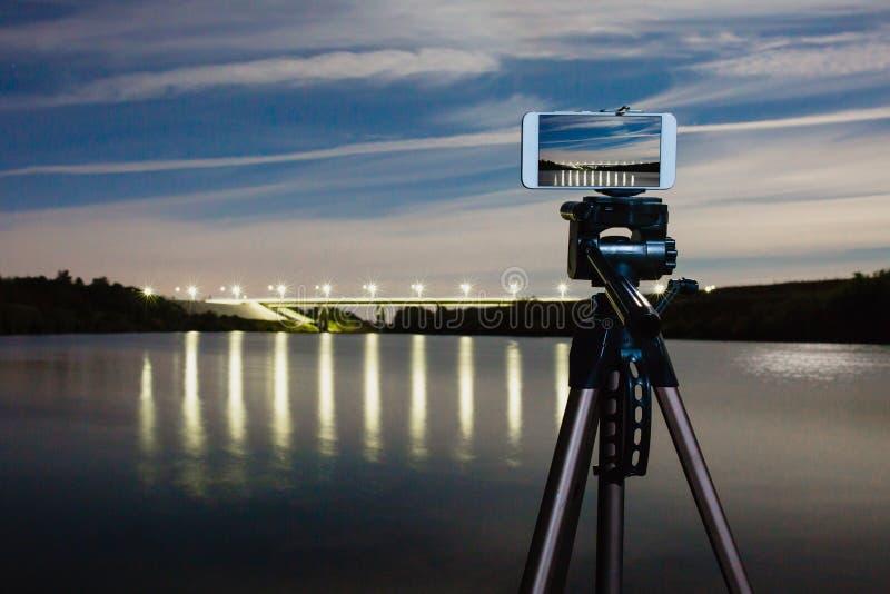 Usando smartphone tenga gusto de la cámara profesional en el trípode a capturar paisaje de la noche foto de archivo libre de regalías