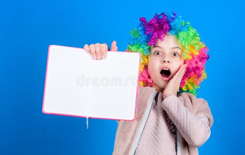 Usando su imaginación Niña en peluca colorida del pelo con la cara sorprendida y la imaginación brillante que sostienen el lib imagen de archivo