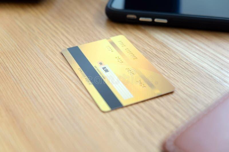Usando um cart?o de cr?dito para pagar em linha, use um smartphone para a compra em linha, uma m?o masculina guarda um cart?o de  imagem de stock