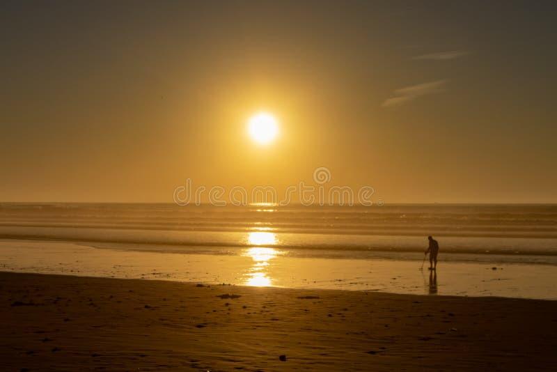 Usando um detector de metais para procurar pelo tesouro escondido em uma praia no por do sol fotos de stock royalty free