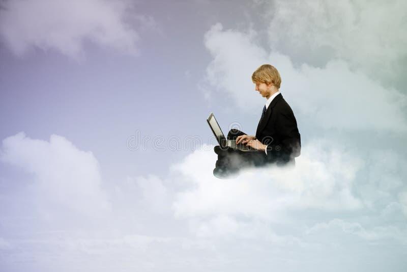 Usando um portátil em nuvens fotos de stock
