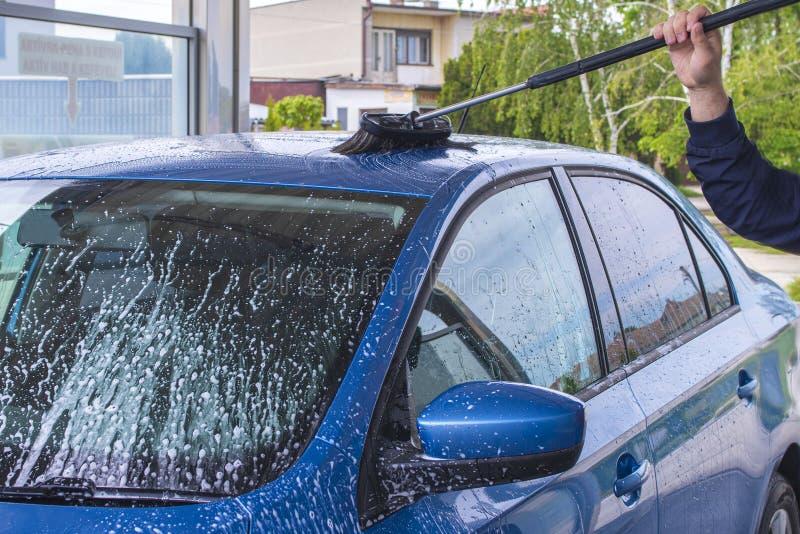 Usando un cepillo para lavar un coche en una instalaci?n de lavado de coche en d?a de verano soleado T?nel de lavado manual con d imagen de archivo libre de regalías