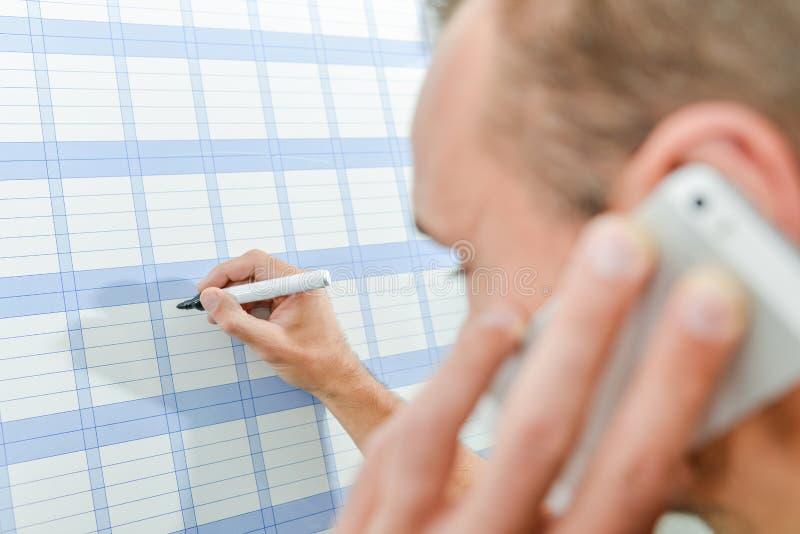 Usando un planificador de la pared fotografía de archivo libre de regalías
