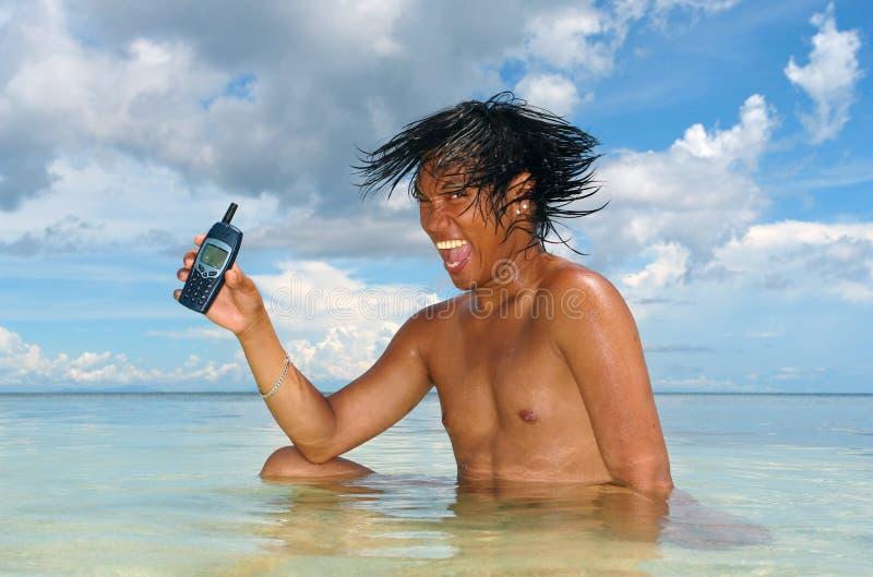 Usando un teléfono celular en un mar tropical. imagen de archivo