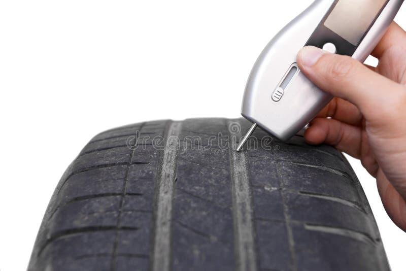 Usando una herramienta de medición digital de la profundidad de pisada del neumático con el neumático viejo foto de archivo