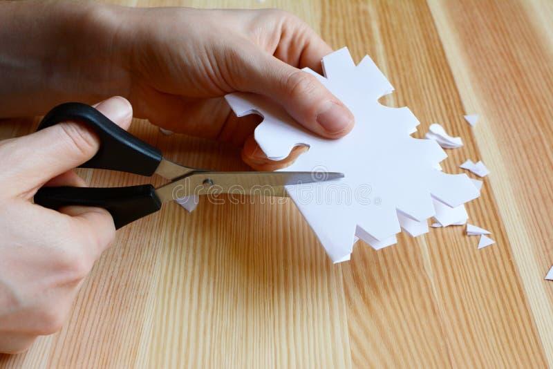 Usar-se scissors para cortar uma forma de papel do floco de neve foto de stock royalty free