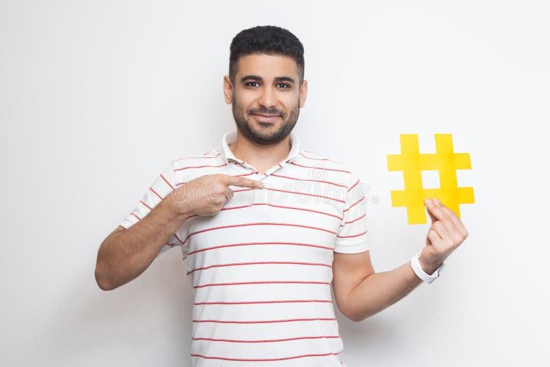 Usate il hashtag? Giovane uomo adulto felice positivo in maglietta che tiene il grande grande segno giallo del hashtag e che indi immagine stock libera da diritti