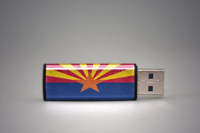 Usb与亚利桑那状态旗子的闪光驱动在灰色背景 免版税库存图片