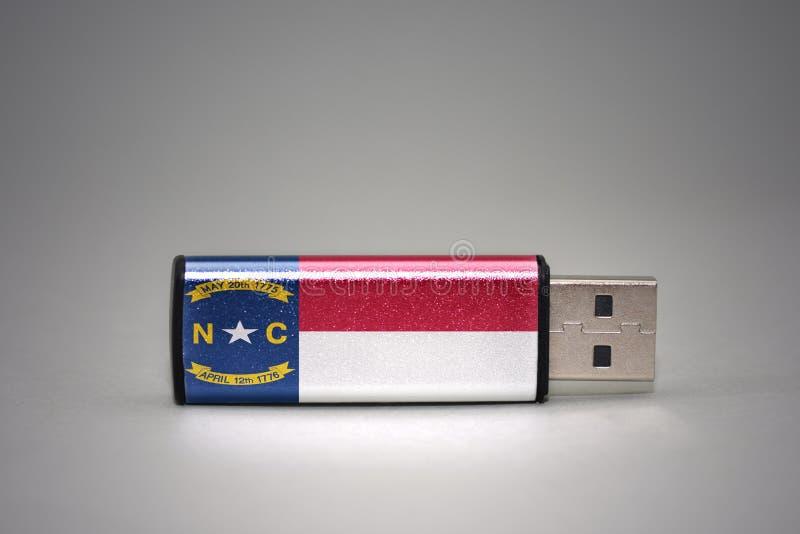 Usb与北卡罗来纳状态旗子的闪光驱动在灰色背景 库存照片