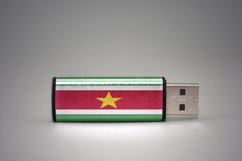 Usb与苏里南的国旗的闪光驱动灰色背景的 免版税库存图片