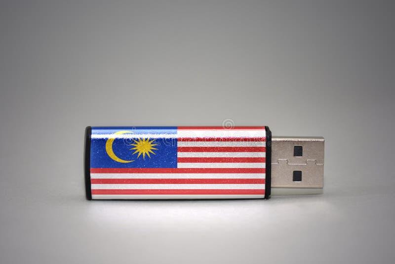 Usb与马来西亚的国旗的闪光驱动灰色背景的 库存图片