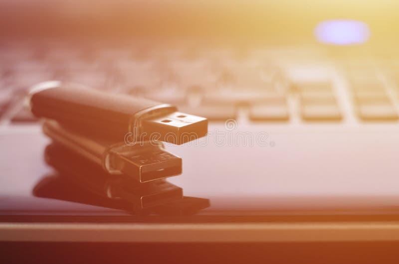 USB bildkort som ligger på den svarta bärbara datorn, case framme av hans tangentbord Lagring för faktiskt minne med USB outpuen arkivfoton