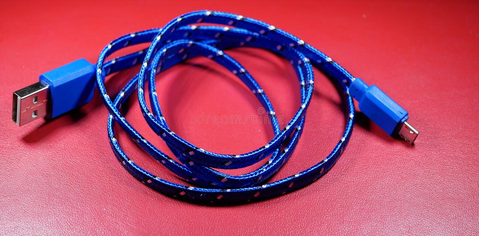 USB cable in blue braid with white dots on red background. stock image