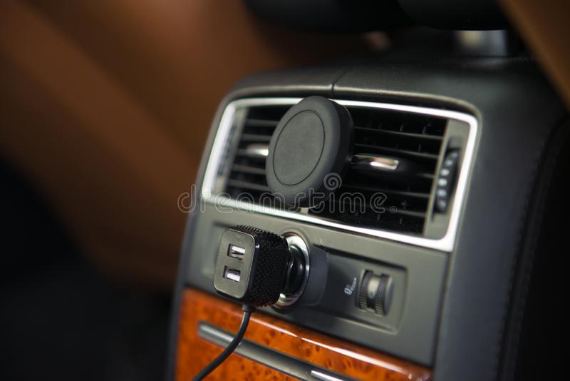 USB charger and magnet A/C mobile phone holder mount in luxury car rear seat. stock images