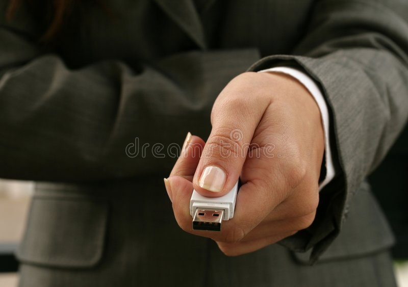 Usb device. A woman in a grey suit holding a usb device stock photos