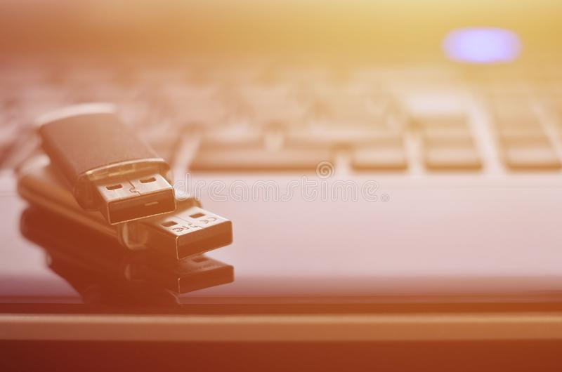 USB flash cards lying on black laptop case in front of his keyboard. Virtual memory storage with USB outpu stock photo