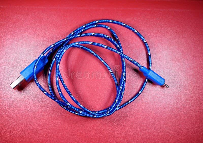 USB-kabel in blauwe vlecht met witte punten op rode achtergrond royalty-vrije stock foto