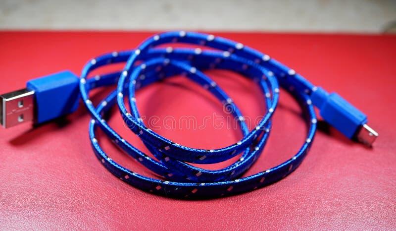 USB-kabel in blauwe vlecht met witte punten op rode achtergrond stock afbeeldingen