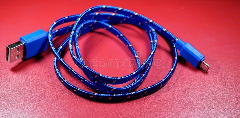 USB-Kabel in der blauen Borte mit weißen Punkten auf rotem Hintergrund stockbild