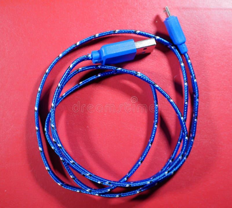USB kabel i blå flätad tråd med vita prickar på röd bakgrund arkivbild
