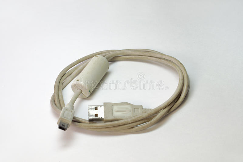 USB-kabel med ferritefiltret, sår in i en cirkel arkivfoto